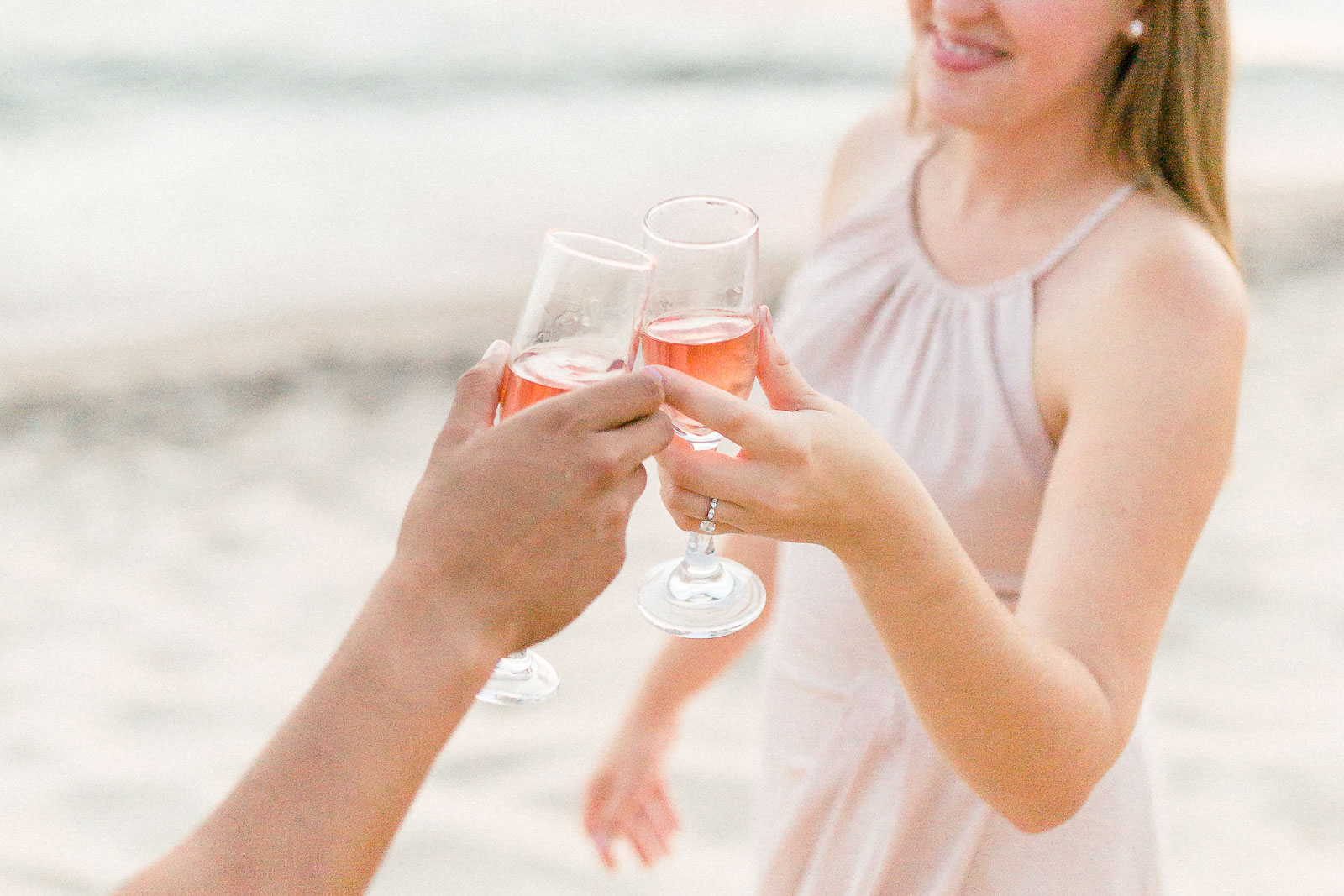 Beach engagement session champagne toast in blush dress